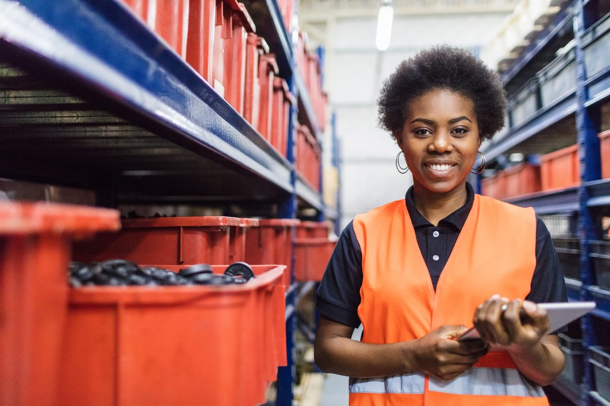 Portrait of african female foremen standing in warehouse aisle with digital tablet. Warehouse supervisor stocktaking in stock room.