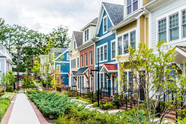 Row of colorful houses, beautiful gardens and side walk in front.